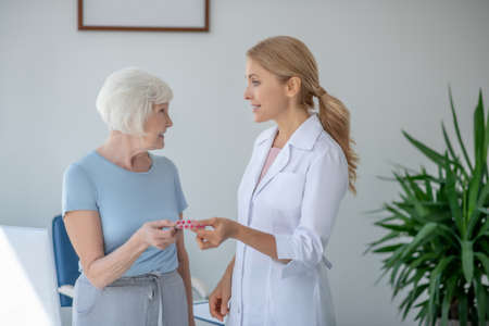 Medication. Smiling blonde doctor giving a blister with pils to a woman
