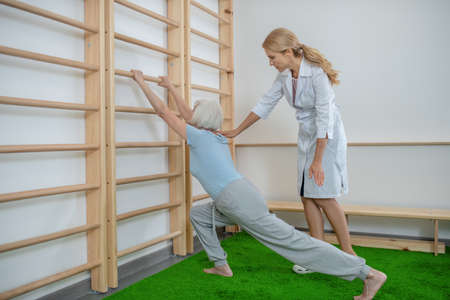 Exercising. Elderly woman doing lunging near a wall-mounted ladder with instructor