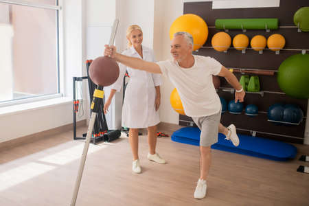 Strength. Grey-haired male patient having a workout in rehabilitation center with a female blonde instructor