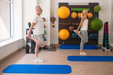 Fitness . A man and a woman in sportswear stretching their legs at fitness class