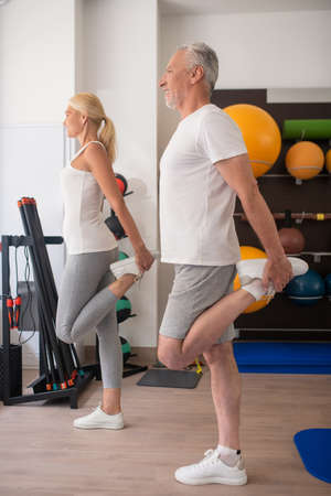 Fitness class. A man and a woman in white sneakers stretching their legs together