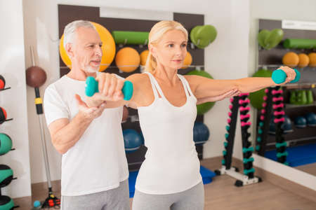 In gym. Male instructor assisting blonde woman working with dumbbells in gym Standard-Bild