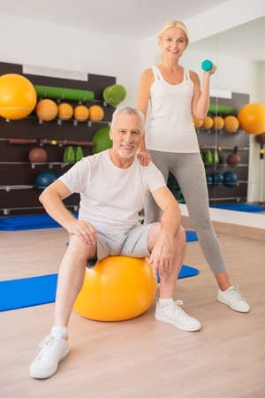 Sporty couple. Man with a ball and a woman with dumbbells exercising together and feeling good