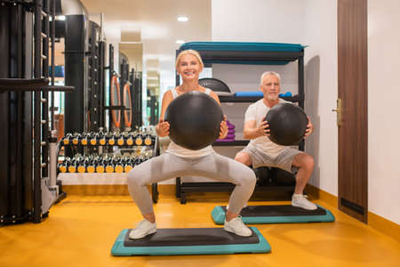 Squats. A man and a woman doing squats with balls