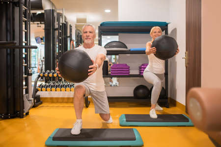 Lungings. A man and a woman doing lunging with balls