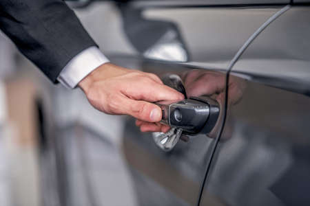 Auto dealership. Close-up of male hand opening car door