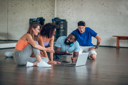 Dance videos. A group of dancers watching dancing videos on the internet
