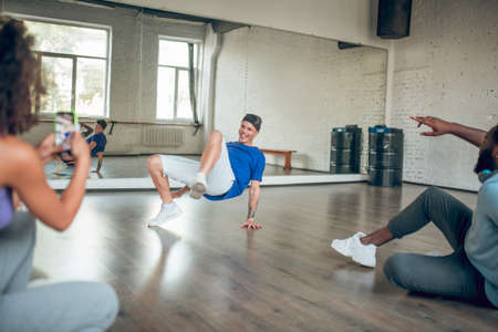 Street dance styles. A trainer teaches his students to do a breaking choreography