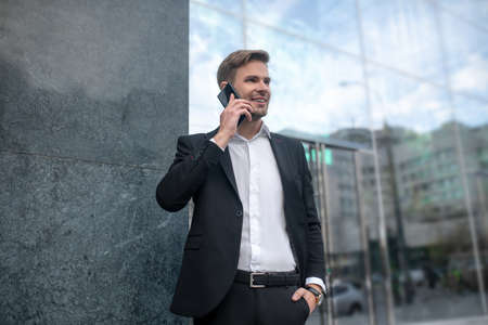 On the phone. Elegant young man in a black suit talking on the phone