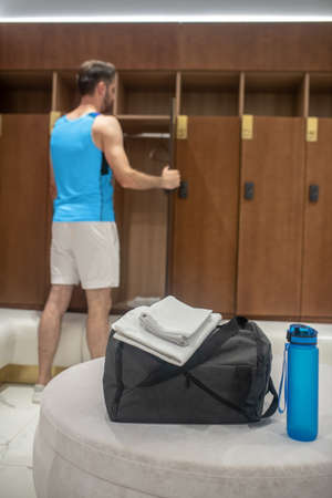 Before workout. Sporty man in blue tshirt standing near the locker in a changing room