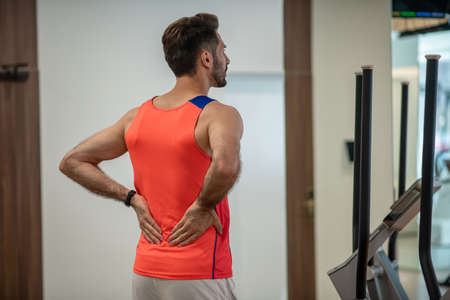 Back pain. Young man exercising in gym and feeling pain in back