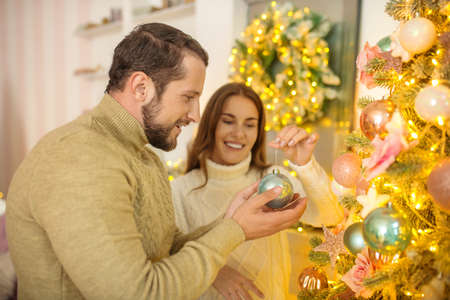 Decorating christmas tree. Young happy couple putting christmas bals on a christmas tree Reklamní fotografie