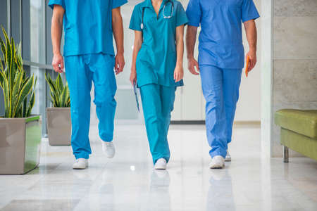 Doctors at work. Close up picture of three doctors walking in the corridor