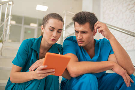 On internet. Two medical workers sitting on the stairs and looking at something on tablet
