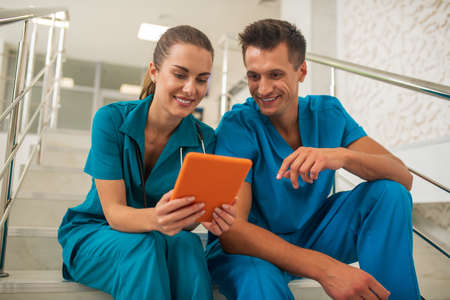 On internet. Two medical workers watching something on internet and discussing