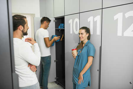 Changeover. Group of people standing in the changing room Banco de Imagens