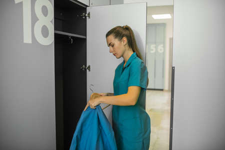 Changing clothes. Long-haired young female doctor putting her clothes to the locker Banco de Imagens