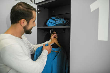 Changing clothes. Young male doctor standing near the locker and holding his uniform