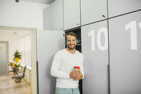 Coffee time. Young bearded man standing near the locker and holding cup with coffee Banco de Imagens