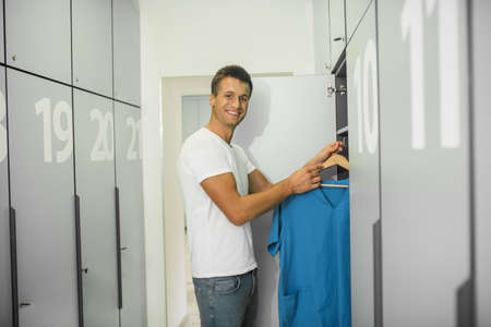 Changeover. Young male doctor in a changing room putting his clothes to the locker