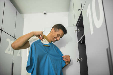Before the shift. Young male doctor taking his uniform out of the locker