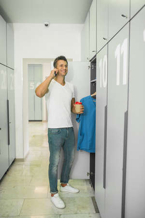Call. Young male doctor in a changing room talking on the phone Banco de Imagens