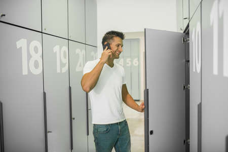 On the phone. Young male doctor in a changing room talking on the phone and looking involved