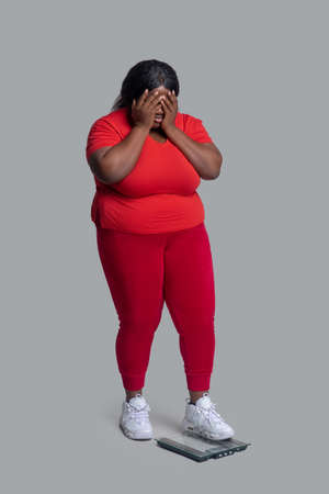 Frustrated. Young dark-skinned woman in red clothes checking weight and feeling frustrated Banco de Imagens