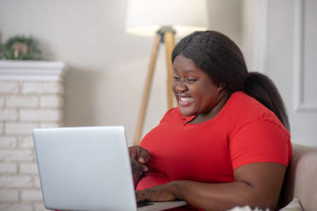 Surprised. African american woman sitting in her room with a laptop and looking surprised