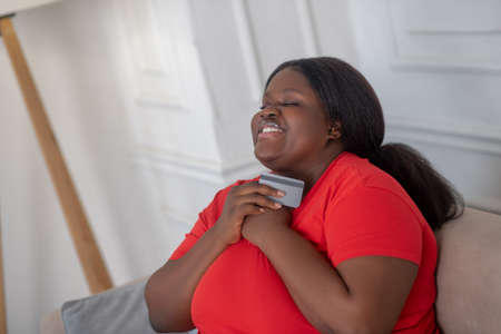 Payment by card. African american woman doing online shopping and looking happy