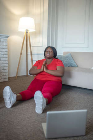 Meditation. Plus size african american woman meditating and looking relaxed