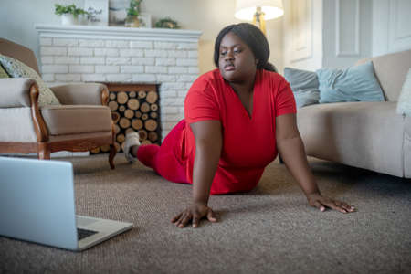 Plank. Plus size african american woman having an online workout and standing in plank Banco de Imagens
