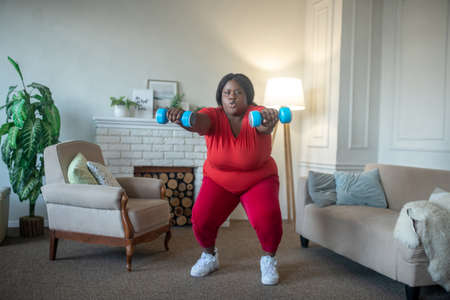 Squats. Plus size african american woman doing squats with dumbbells Banco de Imagens