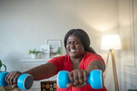 Squats. Plus size african american woman doing squats with dumbbells with tension