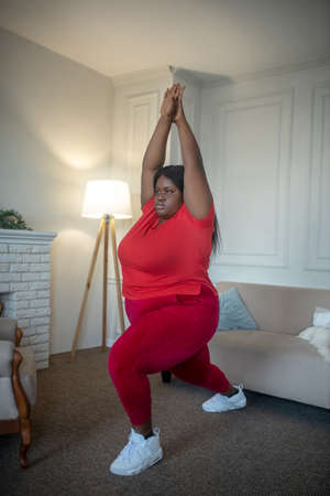 Lunge. Plus size african american woman doing lunges with her arms up Banco de Imagens
