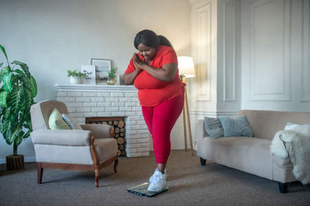 Shocked. Plus size african american woman checking her weight and looking shocked Banco de Imagens