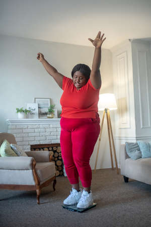 Good result. Plus size african american woman checking her weight and looking happy