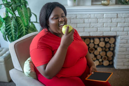 On a diet. Plus size african american woman eating an apple Banco de Imagens