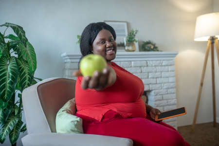 Apple. Plus size african american woman showing an apple in her hand