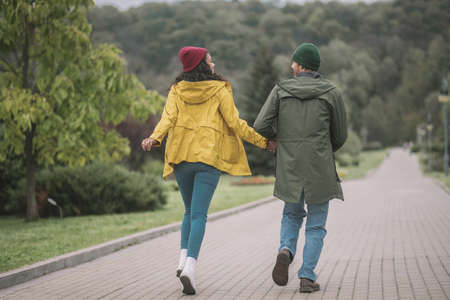 Good mood. Young couple running in the park and looking cheerful