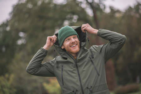Rainy day. Young man in a green coat walking in the rain Banco de Imagens