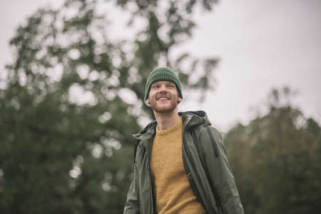 In the park. Close up picture of a young man in a green coat