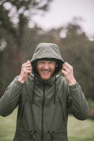 Rainy day. Young man in a green coat walking in the rain and smiling