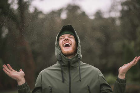 In the rain . Young man in a green coat standing in the rain and smiling