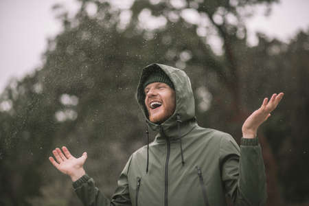 In the rain . Young man in a green coat standing in the rain and smiling Stockfoto