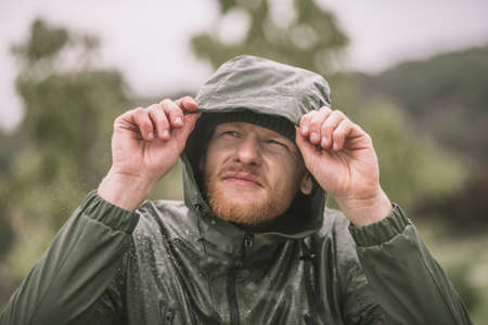 Under the rain. Young bearded man in a hood watching the rain
