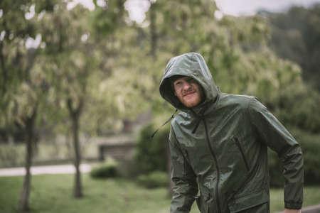 Under the rain. Young bearded man in a hood walking under the rain Banco de Imagens