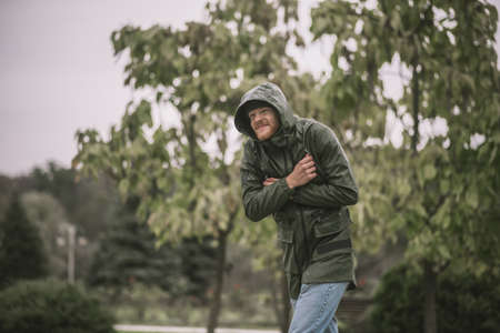 Under the rain. Young bearded man in a hood going under the rain