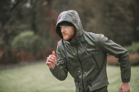 Under the rain. Young bearded man in a hood running under the rain