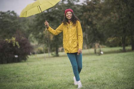 Good mood. Cute mulatta with yellow umbrella looking cheerful